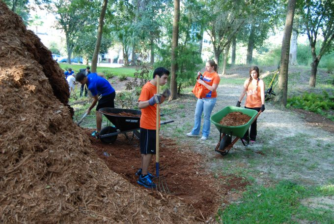 Student volunteers hauling mulch