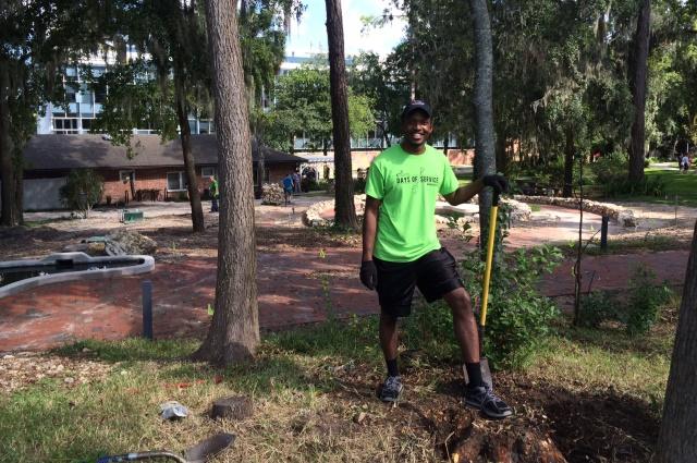 Student volunteer digging hole