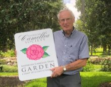 Dr. Tisher holding American Camellia Trail sign